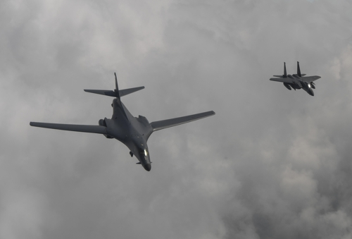 A U.S. B-1B bomber flies over Korea along with a South Korean F-15K fighter