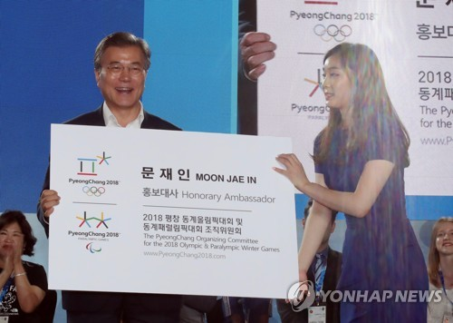 President Moon Jae-in (L) is presented with an enlarged version of his new business card listing him as an honorary ambassador for the PyeongChang Winter Olympic Games by former South Korean Olympic figure skating champion Kim Yu-na (R) in an event held in PyeongChang, located some 180 kilometers east of Seoul, on July 24, 2017. (Yonhap)