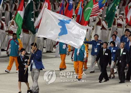 Jointly carrying a unified Korean flag, Lee Kyu-sup (R), a South Korean male basketball player, and Ri Kum-suk (L), a North Korean female footballer, march together on Dec. 1, 2006, at the opening ceremony of the Asian Games in Qatar. (Yonhap)