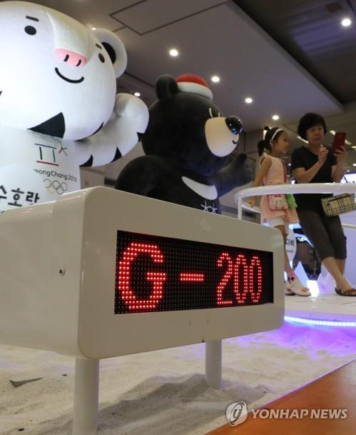 Tourists take pictures beside the mascots of the 2018 PyeongChang Winter Olympics -- Soohorang (L), a white tiger, and Bandabi, an Asiatic black bear -- at Incheon International Airport on July 24, 2017, as the quadrennial sports event is 200 days away. (Yonhap)