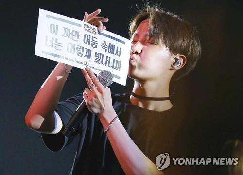 This photo provided by BTS-Trans shows singer J-Hope of K-pop band BTS holding a sign produced by the fan translation community during its Wings world tour. Photo taken by Twitter user @moonsea218. (Yonhap)