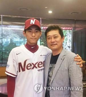 In this file photo provided by the Nexen Heroes baseball club on July 5, 2016, Lee Jung-hoo (L) poses with his father Lee Jong-beom, former Korea Baseball Organization MVP, after being selected in the annual draft. (Yonhap)