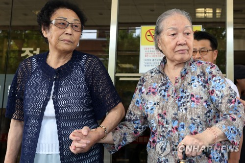 Kim Jae-rim (R), a victim of Japan's forced labor, walks out of the Gwangju District Court on Aug. 11, 2017. The court ordered Mitsubishi Heavy Industries to pay Kim 120 million won in compensation. (Yonhap)