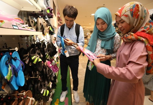 This undated photo provided by Lotte Department Store, South Korea's leading retailer, on Aug. 13, 2017, shows Muslim tourists looking at products at its store in Seoul. (Yonhap)