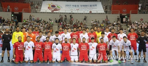 Handball players from South Korea (in white) and Tunisia (in red) pose for photos before the start of their game at the 12th Seoul Cup Handball competition at SK Olympic Handball Gymnasium in Seoul on Aug. 13, 2017. (Yonhap)
