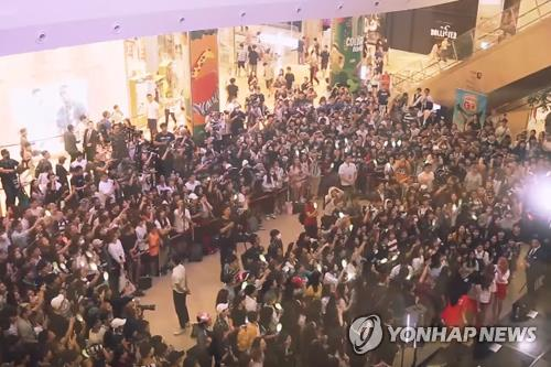This screenshot captured from K-pop group Mamammoo's YouTube page shows a large crowd gathered at a busking performance by the quartet (bottom right) at Lotte World Mall in Seoul on June 25, 2017. (Yonhap)