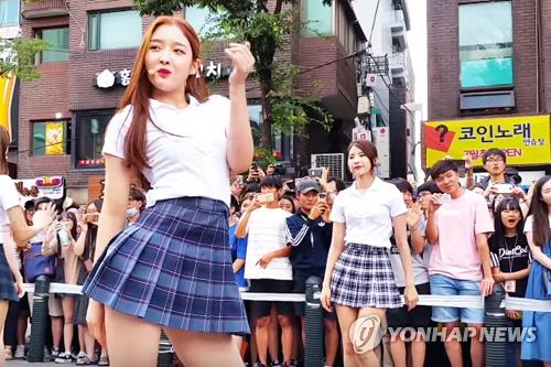 This screenshot captured from MBK Entertainment's YouTube page shows girl group DIA throwing a street performance near Hongik University in western Seoul on June 25, 2016. (Yonhap)