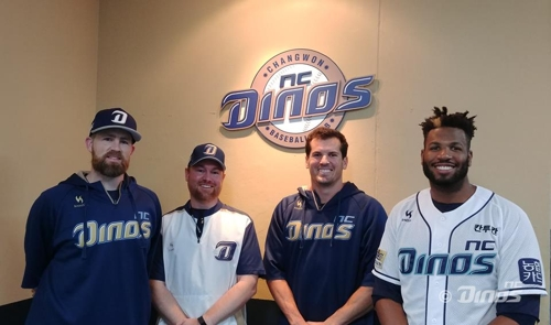 In this file photo provided by the NC Dinos of the Korea Baseball Organization, Patrick Bourgo (second from L), a club official helping the team's foreign players, poses for a picture alongside pitcher Eric Hacker (L), pitcher Jeff Manship (second from R) and infielder Xavier Scruggs. (Yonhap)