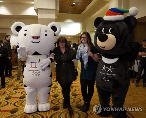 This April 2017 file photo shows Canadian women posing for a photo with the mascots of the 2018 PyeongChang Winter Olympics -- Soohorang (L), a white tiger, and Bandabi, an Asiatic black bear -- during an event at a Toronto hotel to whip up interest for South Korea's first Winter Games that will be held in the host city of PyeongChang, some 180 kilometers east of Seoul. (Yonhap)
