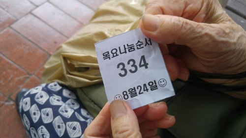 The waiting ticket that Kim So-jae receives on Aug. 24, 2017, shows there are 333 people ahead of her to get 1,500 won and food from three churches in Banpo, southern Seoul. (Yonhap)