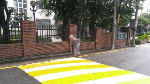 Kim So-jae has a hard time walking with her bent back and aching legs. She walked toward Nul Sa Rang Church in Sinsa-dong, southern Seoul, on Aug. 24, 2017. (Yonhap)