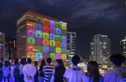 This photo provided by the Ministry of Culture, Sports and Tourism shows people enjoying media art in Seoul Square. (Yonhap)