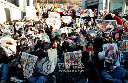 This file photo shows a mob of teenage fans of Seo Tai-ji and Boys on Jan. 25, 1996, staging a protest in front of the home of Seo. Fans called on the trio to resume activities in the wake of the group's retirement announcement. (Yonhap)