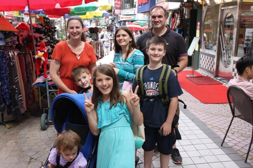 The family of John Bartoli (R), a service member at the 7th Air Force stationed at the Osan base, poses for a photo at the Pyeongtaek International Central Market. (Yonhap)