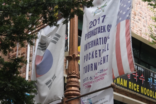 The national flags of South Korea and the United States hang on a pole on the downtown street of the Pyeongtaek International Central Market. (Yonhap)