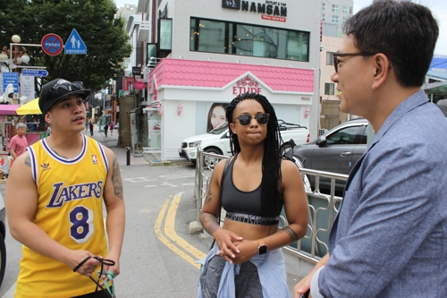 Charles Madayag (L) and his girlfriend Kaila Moffett are interviewed by Yonhap News Agency.(Yonhap)