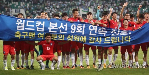 South Korean men's national football players celebrate with a banner after qualifying for the 2018 FIFA World Cup following a scoreless draw against Uzbekistan at Bunyodkor Stdium in Tashkent on Sept. 5, 2017. (Yonhap)