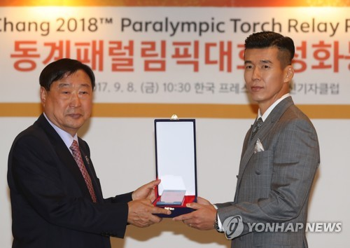 Lee Hee-beom (L), the president of the PyeongChang Organizing Committee for the 2018 Olympic & Paralympic Winter Games, gives a plaque to Sean, a South Korean singer appointed as honorary ambassador for the 2018 PyeongChang Paralympics, during a press conference for the Paralympic torch relay event in Seoul on Sept. 8, 2017. (Yonhap)