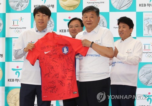 South Korea's national football team head coach Shin Tae-yong (L) holds the national football team jersey with Roh Tae-kang, the second vice minister of the Ministry of Culture, Sports and Tourism, at an event to promote reservations of commemorative coins for the 2018 PyeongChang Olympics at the KEB Hana Bank headquarters in Seoul on Sept. 11, 2017. (Yonhap)