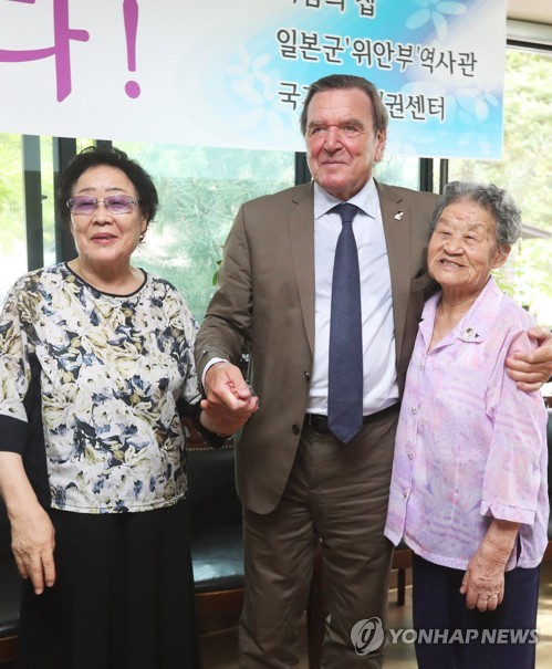 Former German Chancellor Gerhard Schroeder poses for photo with Lee Yong-soo and Park Ok-sun, victims of the wartime sexual enslavement by the Japanese military during the World War II, in the House of Sharing in Gwangju, Gyeonggi Province, on Sept. 11, 2017. (Yonhap)