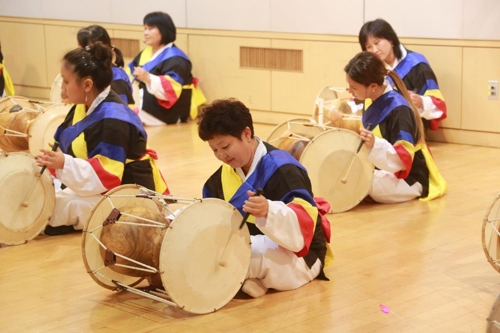 This photo provided by the Overseas Koreans Foundation shows a group of Koryoin teachers practicing a South Korean traditional instrument as part of efforts to learn Korean culture. (Yonhap)
