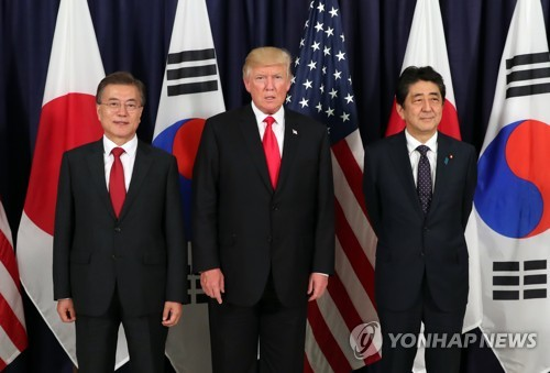 President Moon Jae-in, U.S. President Donald Trump and Japanese Prime Minister Shinzo Abe (from L to R) pose for a photo during a trilateral meeting held in July on the sidelines of a Group of 20 summit. (Yonhap)