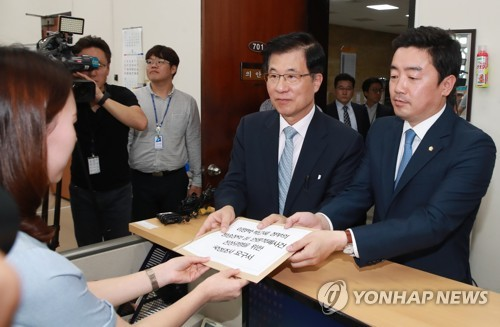 Two lawmakers of the ruling Democratic Party submit to the legislature a motion calling for a parliamentary probe into alleged attempts by past governments to meddle in local broadcasters at the National Assembly in Seoul on Sept. 15, 2017. (Yonhap)