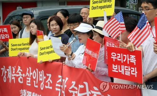In this file photo taken on Aug. 9, 2017, South Korean citizens hold signs condemning the Chinese government's policy on North Korean defectors at the Chinese Embassy in Seoul. (Yonhap)