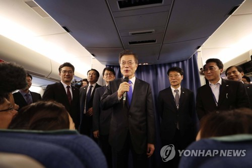 President Moon Jae-in speaks to reporters on the presidential jet on Sept. 22, 2017, on his way home from a visit to New York for the U.N. General Assembly. (Yonhap)