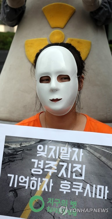 """An environmental activist stages a mask performance to oppose nuclear power during a Seoul rally Sept. 12, 2017, to mark the first anniversary of South Korea's largest recorded earthquake. The quake hit Gyeongju, located 370 kilometers southeast of Seoul, which is home to six nuclear reactors. The picket reads, """"Don't forget the Gyeongju earthquake. Remember Fukushima."""" (Yonhap)"""