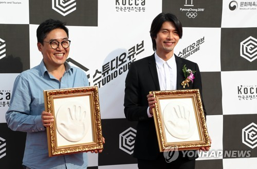 Filmmaker Kim Sung-hoon (L) and actor Hyun Bin pose for photographers after a handprint ceremony in celebration of the opening of Studio Cube in Daejeon, 164 kilometers south of Seoul on Sept. 25, 2017. (Yonhap)