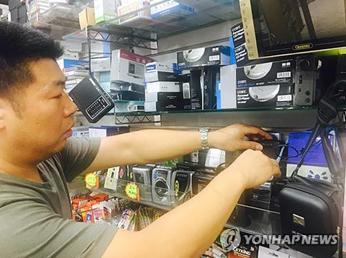 Song Ho-joon, owner of the music store CD Mart in central Seoul, checks the conditions of used portable audio cassette players on Sept. 25, 2017. (Yonhap)