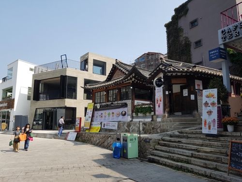 The photo, taken Sept. 26, 2017, shows an old, traditional Korean house, called hanok, turned into a cafe in Samcheong-dong, Seoul while many new and modern buildings can also been in the area. (Yonhap)
