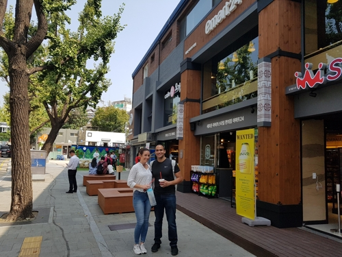 Georgina Sheppard (L) from Britain and Omar Emam, 28-year-old from Egypt, enjoy their drinks from a newly opened stores while walking through Samcheong-dong, one of the oldest part of Seoul, South Korea on Sept. 25, 2017. (Yonhap)