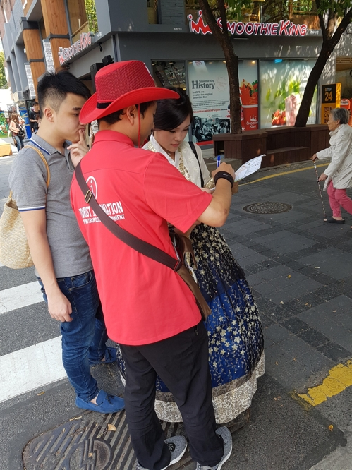 Sohn Hyeong-joon (second from L, in red shirt), a tour guide and English interpreter, helps Isabella Liew and Ken Cheng, both from Malaysia, find their next destination near Seoul's Samcheong-dong on Sept. 25, 2017. (Yonhap)