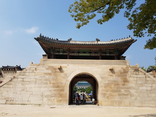 The photo, taken Sept. 25, 2017, shows a group of tourists and visitors gathered outside of the northern gate of Gyeongbok Palace to take their pictures in front of South Korea's presidential office Cheong Wa Dae, meaning blue-tiled house in Korean, that can be seen through the open, arched gate of Gyeongbok Palace. (Yonhap)