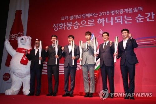 Torch runners for the 2018 PyeongChang Winter Olympics pose with the torches at a ceremony held in Seoul on Sept. 27, 2017. From left: former marathon Olympic silver medalist Lee Bong-joo; singer Sean; former football star Cha Bum-kun; singer Jeong Jin-woon; photographer Cho Sei-hon; and fencer Park Sang-young. (Yonhap)