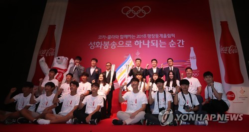 Torch runners for the 2018 PyeongChang Winter Olympics (in back row) pose with South Korean youths who will join them in the relay at a ceremony held in Seoul on Sept. 27, 2017. (Yonhap)