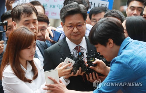 MBC president and CEO Kim Jang-kyom is surrounded by reporters as he goes into the western Seoul district office of the labor ministry for questioning over alleged labor malpractice at the company on Sept. 5, 2017. (Yonhap)