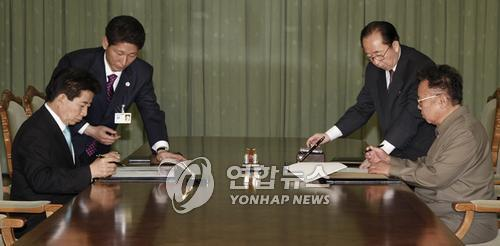 This 2007 photo shows then South Korean President Roh Moo-hyun (L) and North Korean leader Kim Jong-il signing an agreement after the historic second summit between the two sides. (Yonhap)