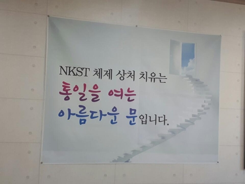 "This photo, taken on Sept 16, 2017, shows a sign hung on a wall of the North Korea System Trauma Healing and Counseling Center. It reads, ""Healing trauma stemming from the North Korean regime's oppressive rule is a beautiful door for unification."" (Yonhap)"