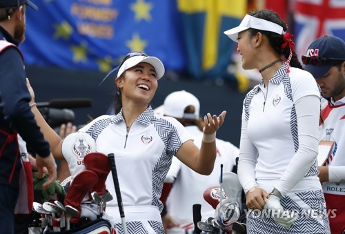 In this Associated Press file photo taken Aug. 19, 2017, Danielle Kang (L) laughs with her U.S. teammate Michelle Wie before their match in the Solheim Cup in West Des Moines, Iowa. (Yonhap)