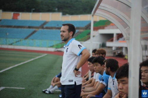 This undated photo provided by TNT FC shows their Portuguese head coach Mario Lemos watching a friendly match in Seoul. (Yonhap)