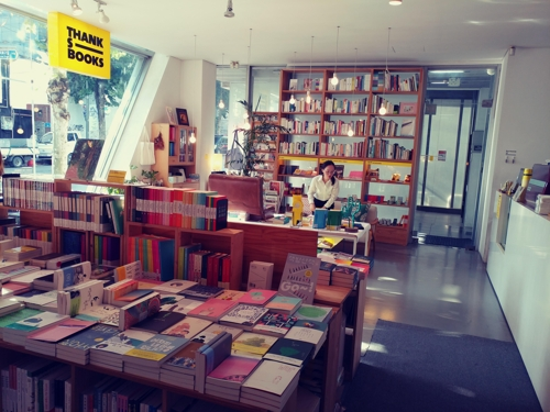 A customer selects a book at ThanksBooks, a bookstore in the Hondage area. (Yonhap)