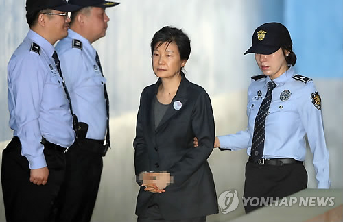 Former President Park Geun-hye is escorted by a guard as she arrives at the courthouse in southern Seoul to attend trial in a bribery and corruption case on Oct. 10, 2017. (Yonhap)