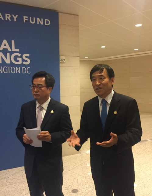 Bank of Korea Gov. Lee Ju-yeol (R), along with Finance Minister Kim Dong-yeon, talk to reporters in Washington on South Korea's currency swap deal with China on Oct. 12, 2017. This photo was provided by the BOK. (Yonhap)