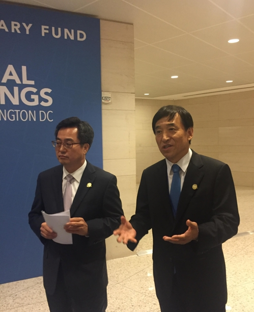 Bank of Korea Gov. Lee Ju-yeol (R) and Finance Minister Kim Dong-yeon talk to reporters in Washington about South Korea's currency swap deal with China on Oct. 12, 2017. This photo was provided by the BOK. (Yonhap)