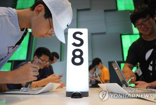 Visitors observe Samsung Electronics Co.'s Galaxy S8 smartphones at an electronics shop in Seoul in this file photo taken July 27, 2017. (Yonhap)