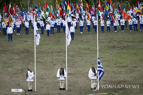 South Korean (R), Olympic and Greek flags are hoisted during the Olympic flame lighting ceremony for the 2018 PyeongChang Games in Olympia, Greece, on Oct. 24, 2017. (Yonhap)