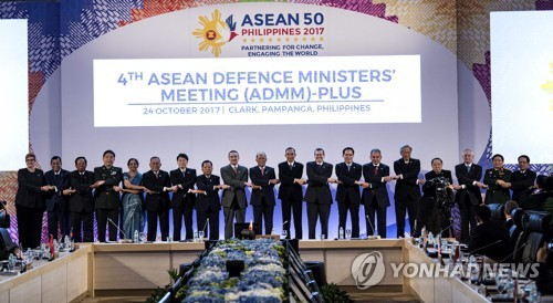The defense chiefs of ASEAN countries and eight dialogue partners -- South Korea, the U.S., China, Japan, Russia, India, Australia and New Zealand -- link arms at a security forum in Clark, the Philippines, on Oct. 24, 2017, in this photo taken by AFP. (Yonhap)